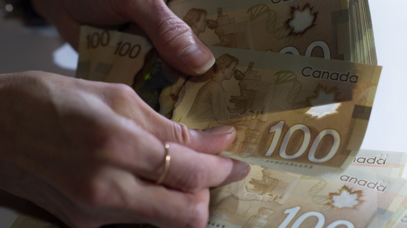 Canadian $100 bills are counted in Toronto, Feb. 2, 2016. (THE CANADIAN PRESS/Graeme Roy)