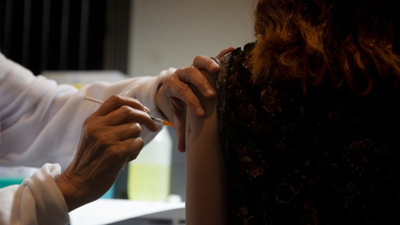 A medical professional administers a booster shot for the coronavirus vaccine, at Clalit Health Services, one of Israel's health maintenance organizations, in Jerusalem, Sunday, Aug. 15, 2021. (AP Photo/Maya Alleruzzo)