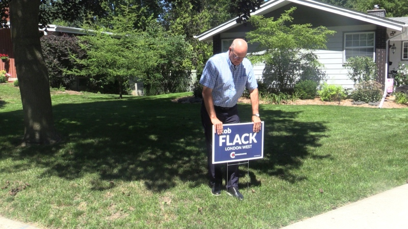 London West Conservative Candidate Rob Flack puts up a lawn sign in North London on the first day of the election campaign Sunday Aug 15, 2021 (Brent Lale / CTV News)