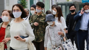 People wearing face masks to protect against the spread of the coronavirus walk on a street in Tokyo Monday, Aug. 16, 2021. (AP Photo/Koji Sasahara)