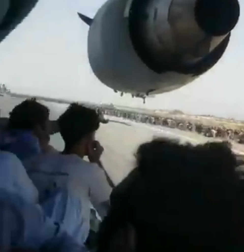 Man clings to side of U.S. aircraft