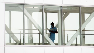A healthcare worker crosses a covered overhead walkway at a hospital in Montreal, Tuesday, August 17, 2021, as the COVID-19 pandemic continues in Canada and around the world. THE CANADIAN PRESS/Graham Hughes