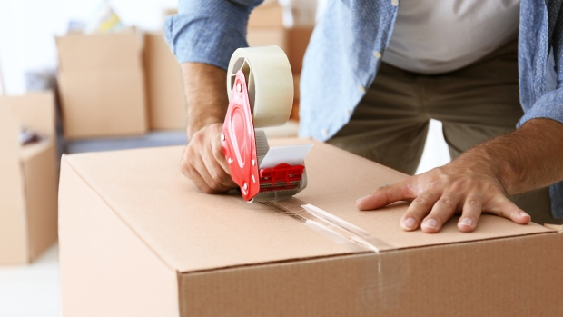 A man tapes up a moving box in a stock image.