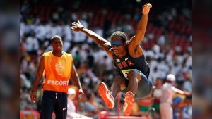 Lex Gillette, right, jumps as his escort, left, looks on during the men's Triple Jump F11 at the Beijing 2008 Paralympic Games in Beijing, China, on Sept. 12, 2008. (Eugene Hoshiko / AP)