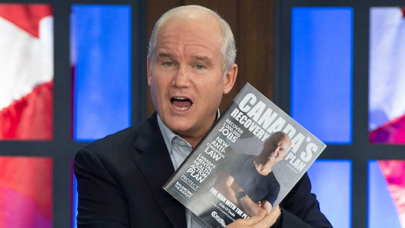 Conservative Leader Erin O'Toole holds up his platorm book as he takes part in a virtual telephone town hall meeting with voters in Nova Scotia from the party's studio Thursday, August 26, 2021 in Ottawa.Canadians will vote in a federal election Sept. 20th.THE CANADIAN PRESS/Ryan Remiorz