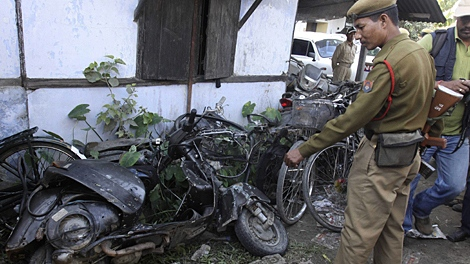 A police officer shows damaged vehicles at a police station near which a blast took place in Nalbari, about 75 kilometers (47 miles) west of Gauhati, India, Sunday, Nov. 22, 2009. (AP / Anupam Nath)