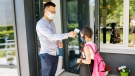 A staff member checks a student's temperature before entering the school. (Photo by Yan Krukov from Pexels)