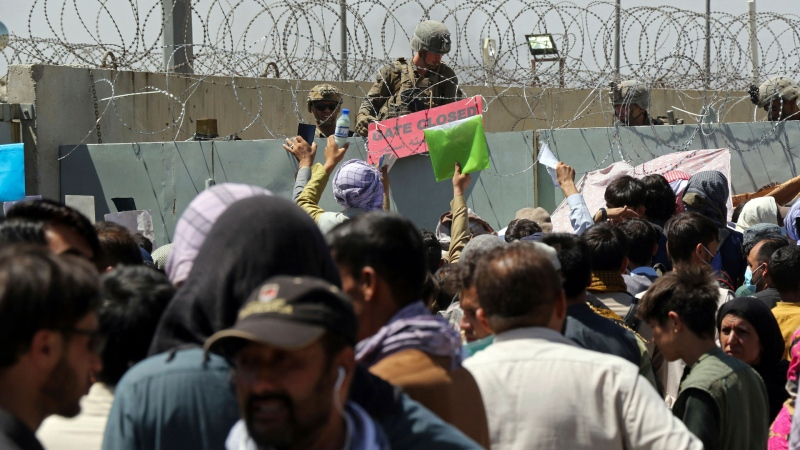 A U.S. soldier holds a sign indicating a gate is closed as hundreds of people gather some holding documents, near an evacuation control checkpoint on the perimeter of the Hamid Karzai International Airport, in Kabul, Afghanistan, Thursday, Aug. 26, 2021. (AP Photo/Wali Sabawoon)