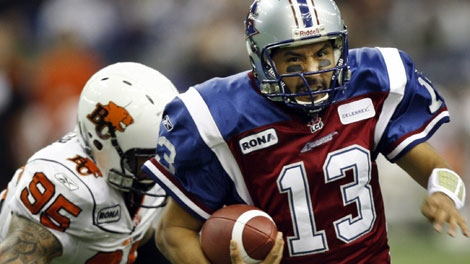 Montreal Alouettes quarterback Anthony Calvillo(13) tries to get away from B.C.Lions defensive end Ricky Foley during first quarter CFL Eastern Final football action at Olympic Stadium Sunday, November 22, 2009 in Montreal.THE CANADIAN PRESS/Ryan Remiorz