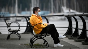 A man wears a face mask near the waterfront in Vancouver. (Shutterstock)