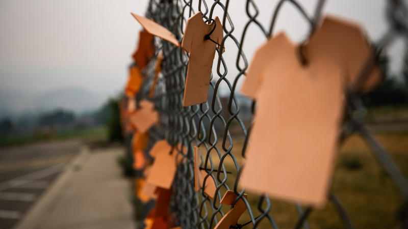 Cutouts of orange T-shirts are hung on a fence outside the former Kamloops Indian Residential School, in Kamloops, B.C., on Thursday, July 15, 2021. (Darryl Dyck / THE CANADIAN PRESS)