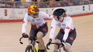 Canada's Monique Sullivan (left) reaches out to compatriot Kate O'Brien as they win gold and silver, respectively, in the women's sprint during track cycling at the Pan Am games in Milton, Ont., July 19, 2015. THE CANADIAN PRESS/Chris Young