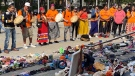 A temporary memorial for victims of Canada's residential schools is blessed by Indigenous elders in a pipe ceremony in Calgary on Aug. 26, 2021. Orange shirts are often worn on Sept. 30 to honour residential school survivors. (THE CANADIAN PRESS/Bill Graveland)