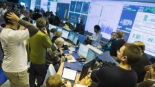Scientists gather at the European Organization for Nuclear Research (CERN) data quality satellite control centre of the ATLAS detectors during the restart of the Large Hadron Collider (LHC) in Meyrin, near Geneva, Switzerland, Monday, Nov. 23, 2009. (AP / Keystone, Laurent Gillieron)