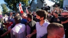 Liberal Leader Justin Trudeau is escorted by his RCMP security detail as protesters shout and throw small rocks while leaving a campaign stop at a local micro brewery during the Canadian federal election campaign in London Ont., on Sept. 6, 2021. THE CANADIAN PRESS/Nathan Denett