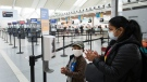 """People use mandatory hand sanitizer and masks at Toronto's Pearson International Airport for a """"Healthy Airport"""" during the COVID-19 pandemic in Toronto on Tuesday, June 23, 2020. THE CANADIAN PRESS/Nathan Denette"""