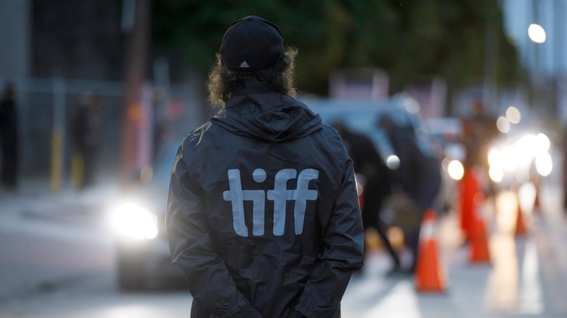 An attendant stands by as cars enter Toronto International Film Festival's Visa Skyline Drive-In at CityView for the TIFF drive-in premier of David Byrne's American Utopia in Toronto, Thursday, Sept. 10, 2020. THE CANADIAN PRESS/Cole Burston