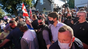 Liberal Leader Justin Trudeau is escorted by his RCMP security detail as protesters shout and throw rocks while leaving a campaign stop at a local micro brewery during the Canadian federal election campaign in London Ont., on Monday, September 6, 2021. THE CANADIAN PRESS/Nathan Denette
