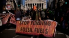 An Extinction Rebellion climate change activist holds a banner backdropped by the Bank of England, at left, and the Royal Exchange, centre, in the City of London financial district, on Sept. 2, 2021. (Matt Dunham / AP)