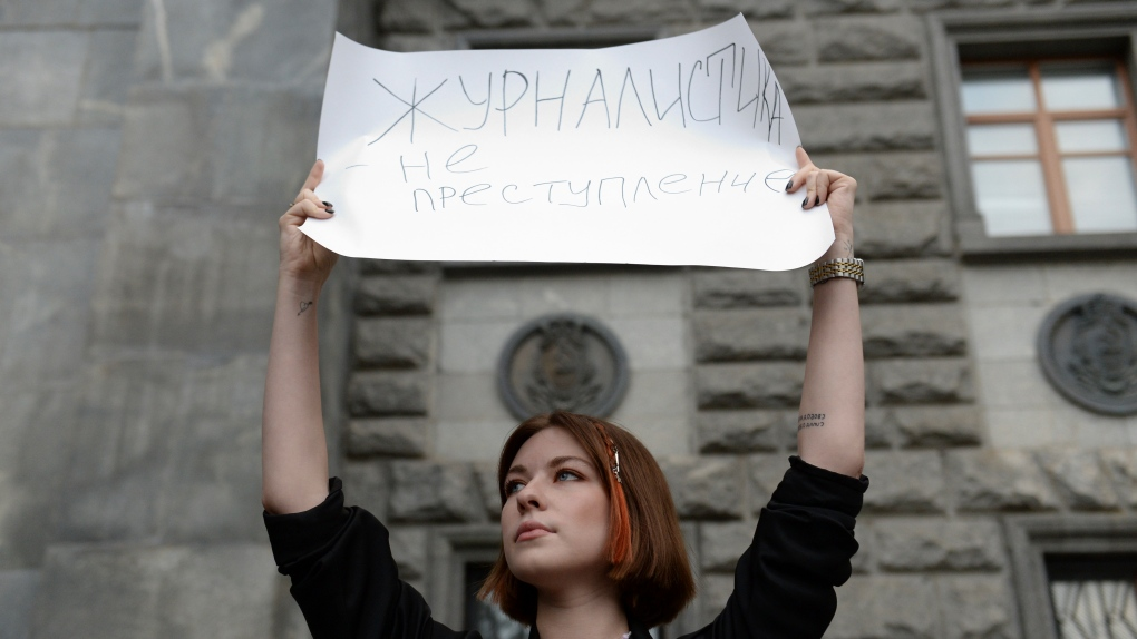 A journalist holds a poster at a protest