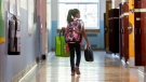 A young girl walks in the hallway on the first day of school in Montreal, Tuesday, August 31, 2021, as the COVID-19 pandemic continues in Canada and around the world. (THE CANADIAN PRESS / Graham Hughes)