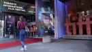 A pedestrian walks past the TIFF Bell Lightbox headquarters of the 2021 Toronto International Film Festival on day one of the festival, Thursday, Sept. 9, 2021, in Toronto. (AP Photo/Chris Pizzello)