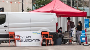 People line up to get a COVID-19 vaccine at a pop-up clinic in Vancouver. (Shutterstock)