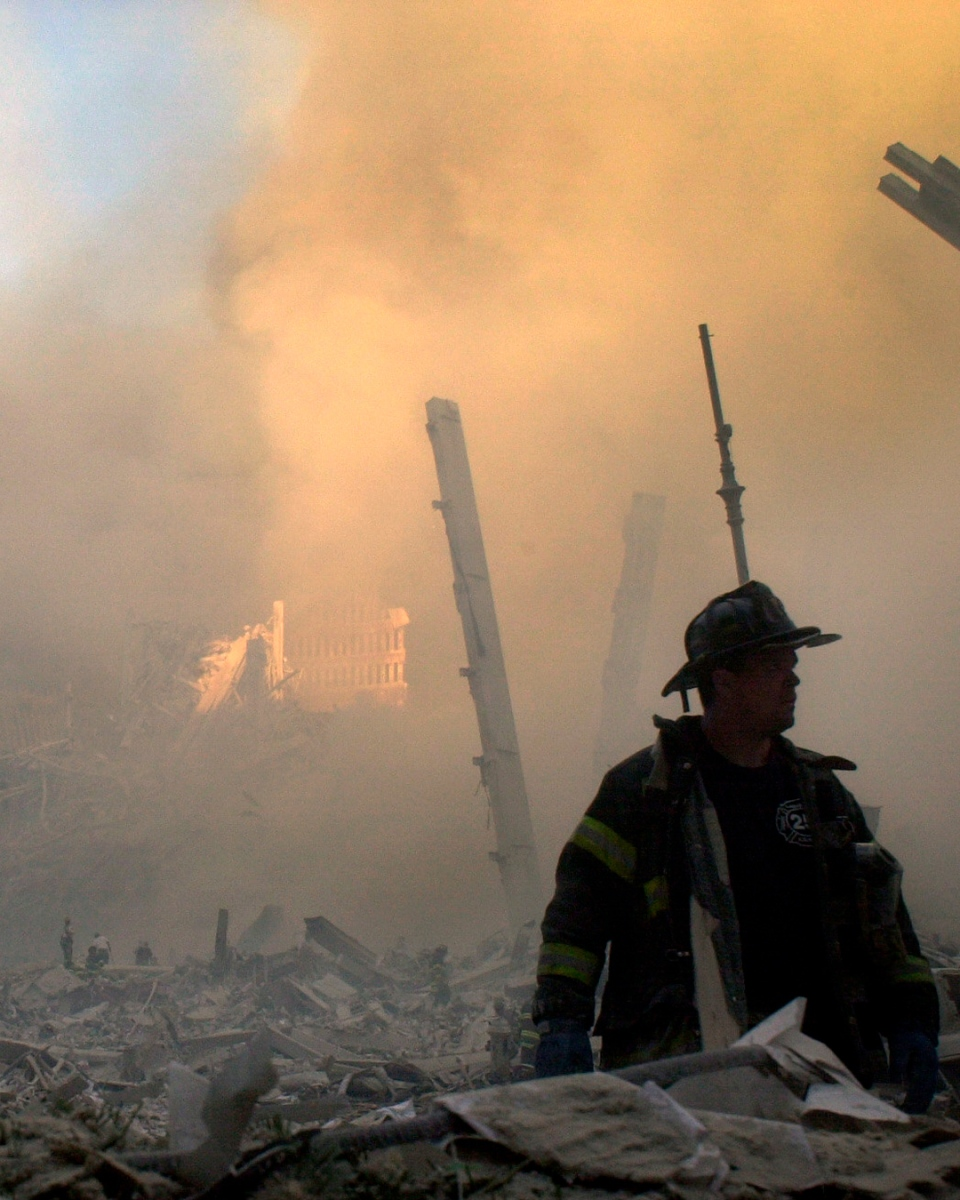 A firefighter moves through piles of debris