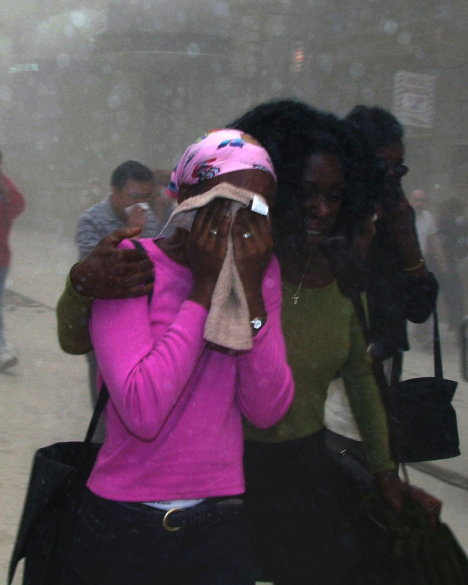 People cover their faces as they escape
