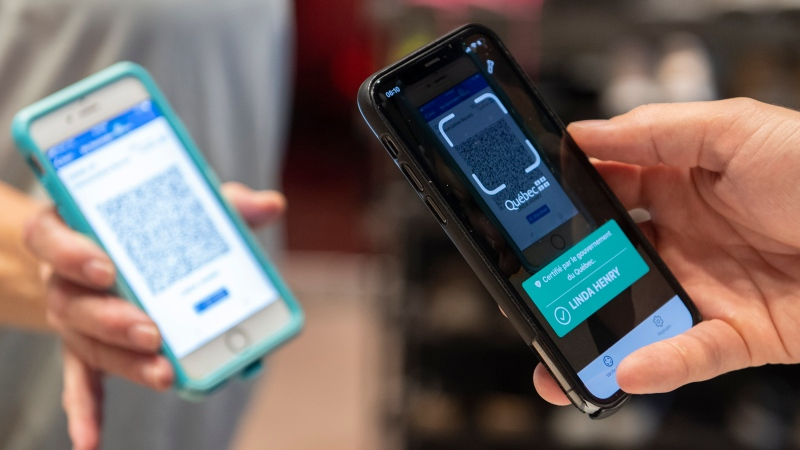 Linda Henry has her COVID-19 QR code scanned by Jonathan Gagne, manager of Orangetheory Fitness in Montreal, Wednesday, September 1, 2021, as the Quebec government's COVID-19 vaccine passport comes into effect. (THE CANADIAN PRESS / Graham Hughes)