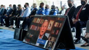 A screen displays a video of former President George W. Bush during an event to commemorate the 20th anniversary of the Sept. 11, 2001, terrorist attacks, Saturday, Sept. 11, 2021, in Springfield, Va. (AP Photo/Luis M. Alvarez)