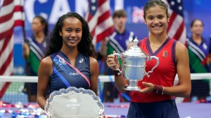 Leylah Fernandez, of Canada, left, and Emma Raducanu, of Britain, pose for photos after Raducanu defeated Fernandez in the women's singles final of the US Open tennis championships, Saturday, Sept. 11, 2021, in New York. (AP Photo/Seth Wenig)