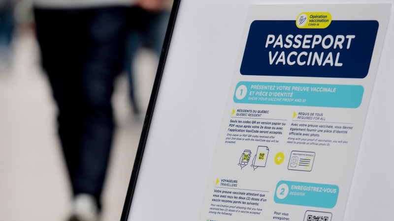 People walk by a sign at a restaurant advising customers of Quebec's Covid-19 vaccine passport in Montreal, Monday, Sept. 6, 2021, as the COVID-19 pandemic continues in Canada and around the world. THE CANADIAN PRESS/Graham Hughes