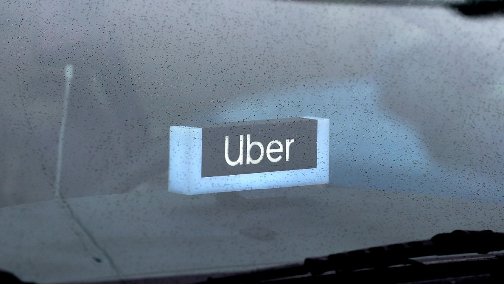 An Uber sign is displayed inside a car