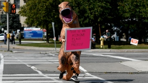 A counter-protester wearing a dinosaur suit holds a sign expressing their displeasure with people gathered outside the Ottawa Hospital Civic Campus to protest COVID-19 vaccinations and health measures, in Ottawa, on Monday, Sept. 13, 2021. (Justin Tang/THE CANADIAN PRESS)