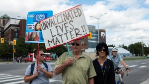 People arrive for a protest against COVID-19 vaccinations and health measures, outside the Ottawa Hospital Civic Campus in Ottawa, on Monday, Sept. 13, 2021. (Justin Tang/THE CANADIAN PRESS)