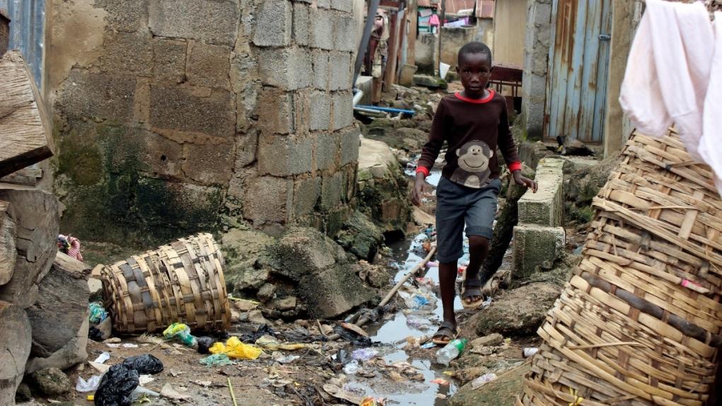 A boy walks past sewage around houses in Abuja