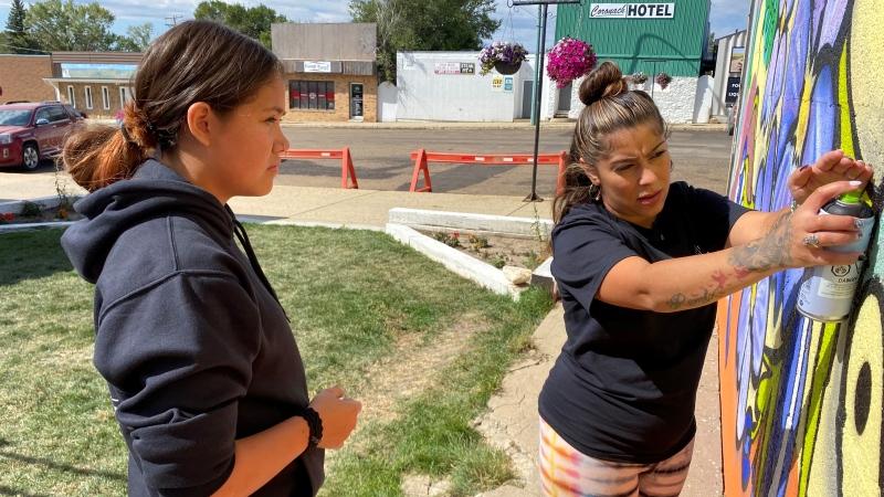 Stephanie Bellefleur (right) shows her teenage mentee, Amanda, techniques with an aerosol can. (Gareth Dillistone/CTV News)