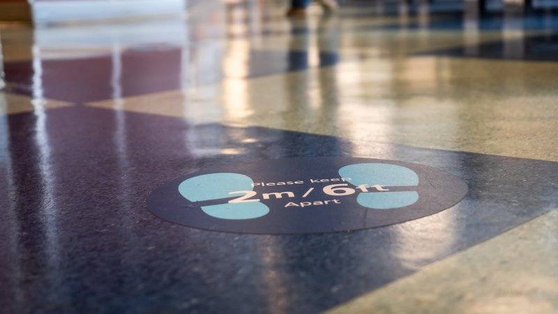 Sign on floor at BC Ferries terminal asking people to keep a physical distance during the COVID-19 pandemic. (Shutterstock)