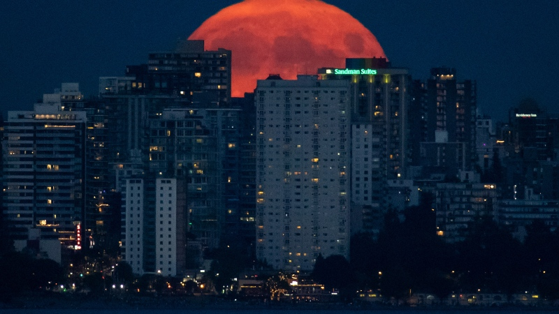 A full moon rises behind the downtown skyline in Vancouver, on Friday, July 23, 2021. (Darryl Dyck / THE CANADIAN PRESS)