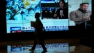 A woman walks by a TV screen showing CCTV broadcasting a news of Chinese astronauts sit inside the Shenzhou-12 manned spacecraft preparing to return to earth, at a shopping mall in Beijing, Thursday, Sept. 16, 2021. (AP Photo/Andy Wong)