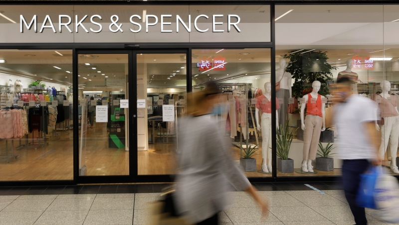 Shoppers pass a branch of Marks and Spencer in London, Tuesday, Aug. 18, 2020. (AP Photo/Kirsty Wigglesworth)
