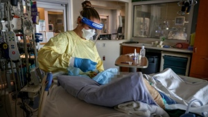 A registered nurse works with a COVID-19 patient on the Intensive Care Unit at Foothills Medical Centre on Sept. 10, 2021. (Alberta Health Services)