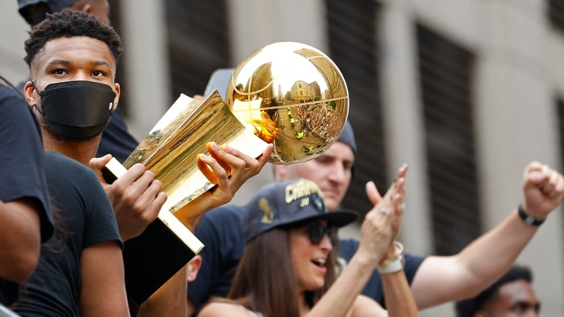 Milwaukee Bucks' Giannis Antetokounmpo, left, holds up the NBA Championship Trophy during a parade for the basketball team's NBA Championship win, on July 22, 2021. (Jeffrey Phelps / AP)