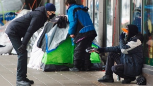 A man chats with a homeless person at a small tent city on St. Catherine street, Wednesday, January 27, 2021 in downtownMontreal.THE CANADIAN PRESS/Ryan Remior