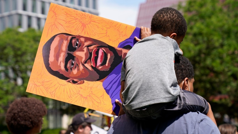 A young boy holds a George Floyd poster after former Minneapolis police officer Derek Chauvin was sentenced, on June 25, 2021. (Jim Mone / AP)