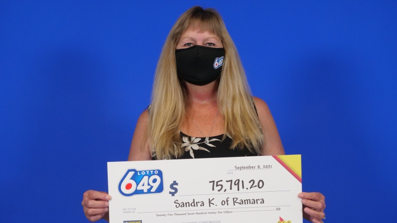 Sandra Kaspar, 59, of Ramara Township, Ont., holds her big cheque at the OLG Prize Centre in Toronto. (OLG)