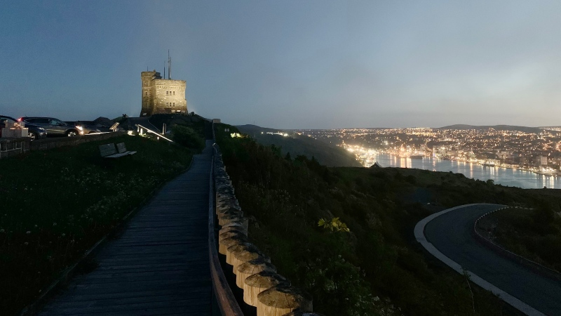 People sit in their vehicles to take in the view from the Cabot Tower parking lot on Signal Hill as a fog creeps in and the lights of St. John's sparkle in the background on Monday June 14, 2021. THE CANADIAN PRESS/Sarah Smellie
