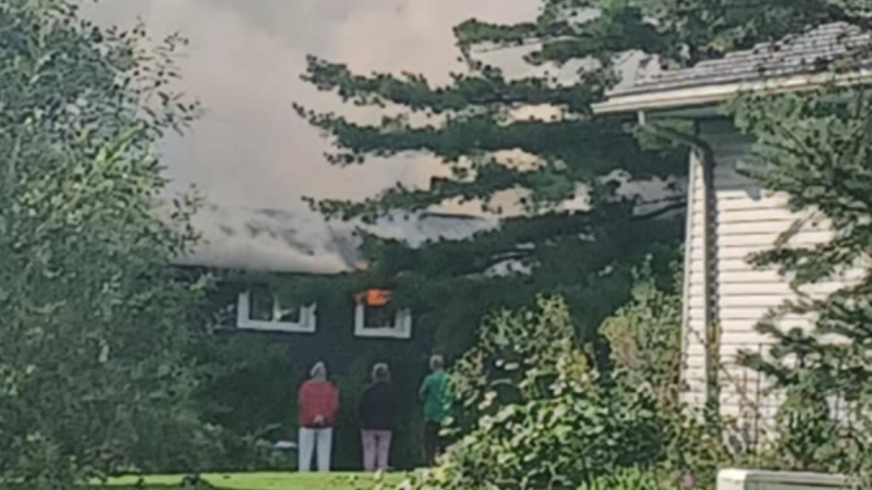 People watch as flames and smoke overwhelm a home in Coldwater, Ont., on Wed., Sept. 15, 2021 (Photo Courtesy: Chris Lamoureux)