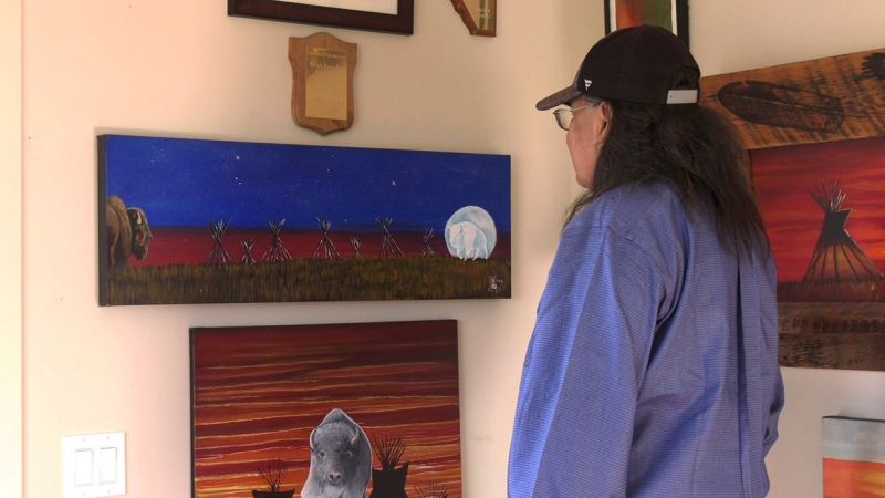 Indigenous artist Keevin Rider looks at his painting titled White Buffalo Moon that's 1 of 17 peace's featured at Southcentre Mall's Art Corner